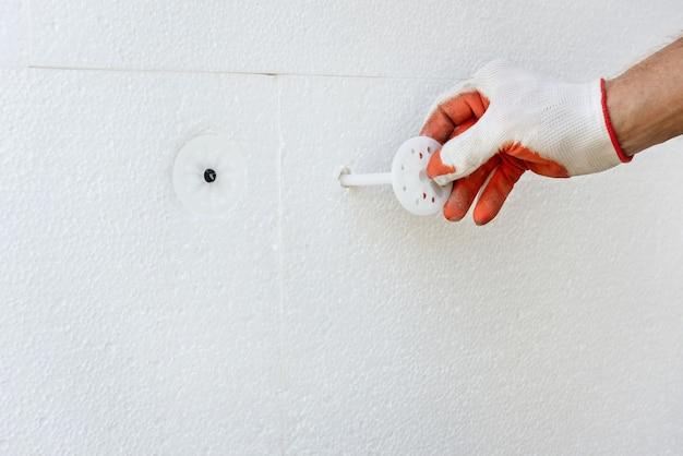Утепление дома пенопластом. рабочий фиксирует пенополистироловую доску пластиковыми дюбелями.