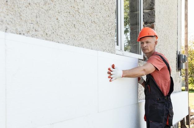 ポリフォームによる家の断熱。作業員はファサードに発泡スチロールの板を取り付けています。