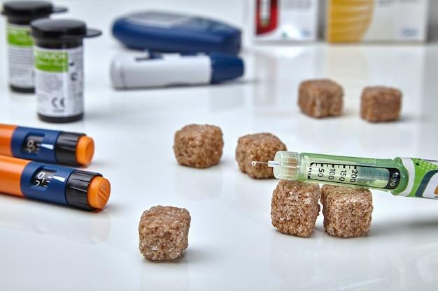 Инсулиновые ручки и капля инсулина на кончике иглы.