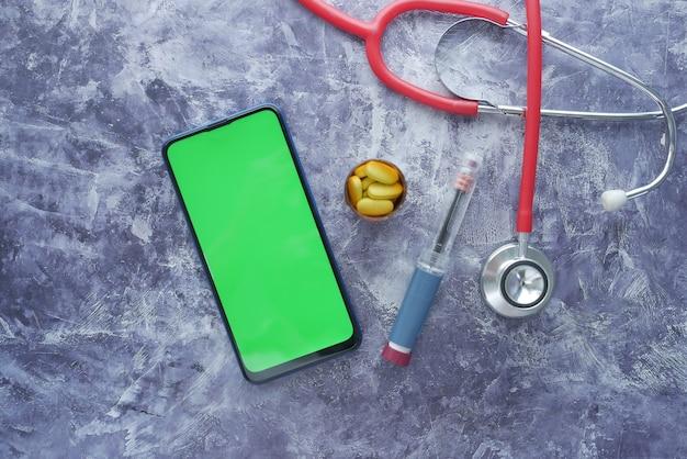 Инсулиновые ручки и таблетки смартфона и стетоскоп на черной поверхности