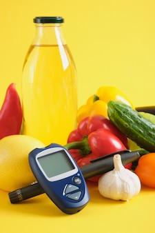 Инсулиновая шприц-ручка, цифровой глюкометр и овощи на желтом фоне. питание при диабете