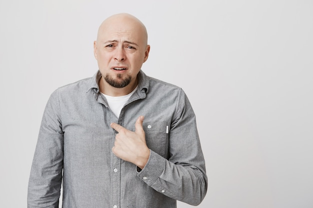 Insulted bald man pointing himself