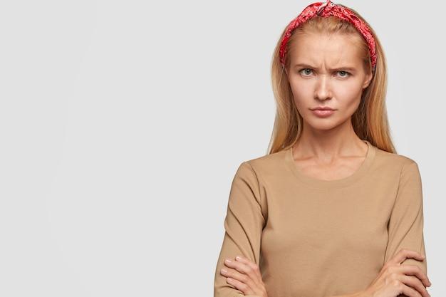 Оскорбленная молодая блондинка позирует у белой стены