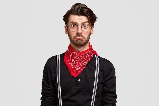 Uomo europeo insultato dispiaciuto con barba folta, labbra curve inferiori, taglio di capelli alla moda, indossa una camicia alla moda con bandana rossa