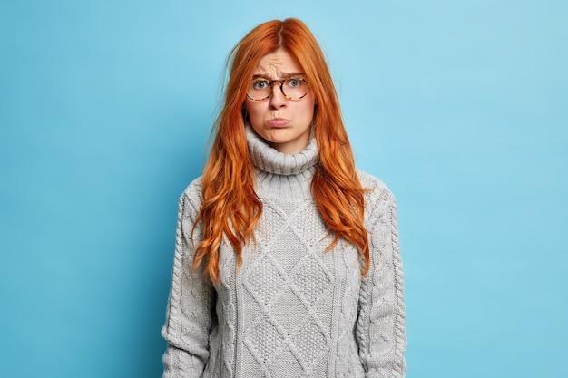 侮辱された不機嫌な生姜ヨーロッパの女性は、表情を怒らせ、唇を財布に入れ、灰色のセーターを着て眼鏡をかけて泣きたい。