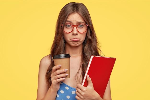 L'allievo insultato contrasta le labbra con offesa, beve caffè da asporto essendo di cattivo umore dopo aver fallito l'esame