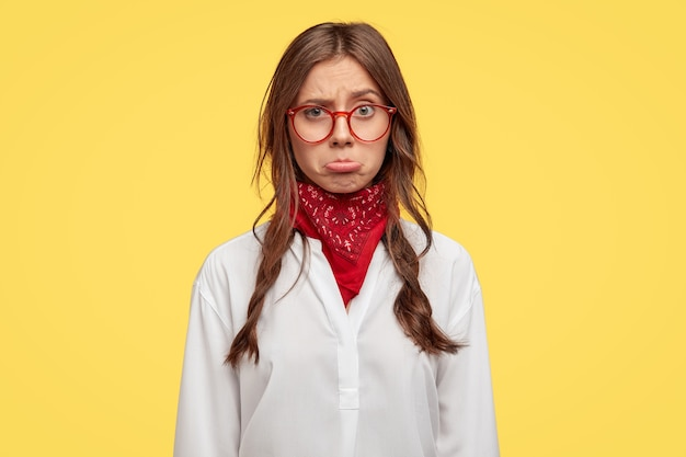 侮辱された悲しい女性は、ひどいニュースに腹を立てて下唇を財布に入れ、2つのわずかに櫛でとかされたひだを持ち、光学ガラスと白いシャツを着て、否定的な感情を表現し、黄色い壁の上のモデル
