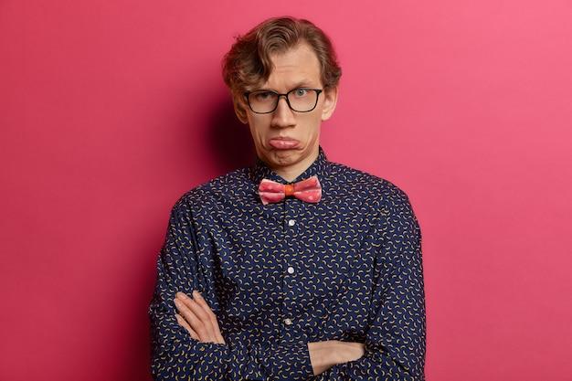 Il giovane uomo caucasico insultato tiene le mani incrociate sul corpo, porta il labbro inferiore, ha un'espressione scontenta, indossa abiti formali, sente commenti spiacevoli, ha i capelli mossi, isolato su un muro rosa.