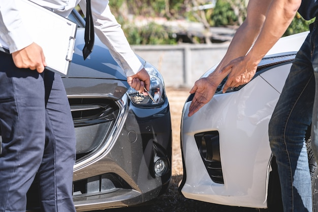 Insurance agent and customer assessed negotiation, checking and signing on report claim form process after accident collision, traffic accident and insurance concept