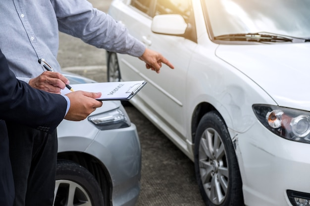 Страховой агент проверяет поврежденный автомобиль и подает заявку на участие в конкурсе после аварии
