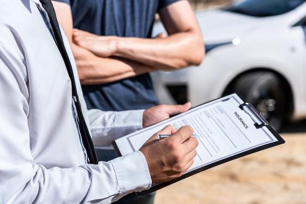 Страховой агент рассматривает автокатастрофу и оценивает переговоры, проверяет и подписывает форму заявления о претензии после столкновения, концепция несчастного случая и страхования