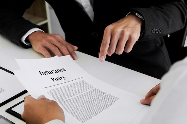 보험 에이전트는 고객과 상담하여 정책 양식에 서명하는 것을 설명합니다.