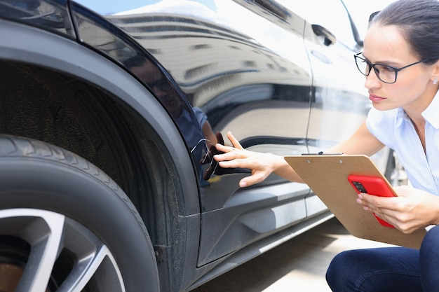 손상된 검은색 자동차 보험 개념 근처에 보험 양식을 작성하는 보험 대리인