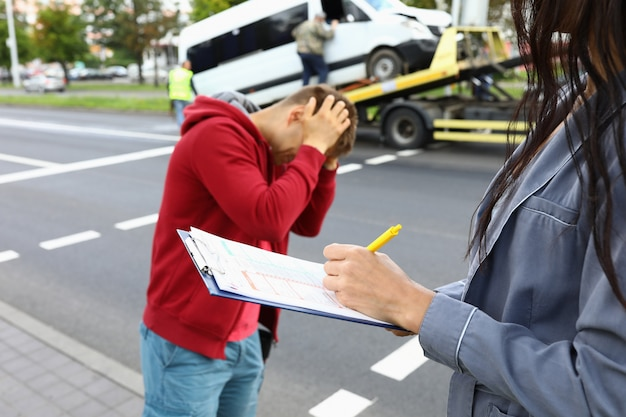 自動車事故ドライバーが隣に立って頭を抱えた後、保険代理店が保険に記入する