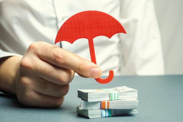 An insurance agent holds a red umbrella