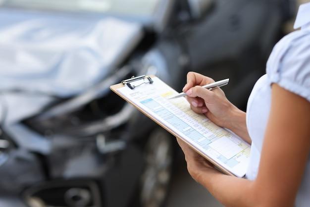 보험 대리인은 손상된 차량 자동차 보험 개념을 검사합니다.