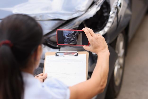 보험 대리인은 자동차 사고 개념 후 충돌한 자동차 손상 평가에 대한 손상을 촬영하고 있습니다.