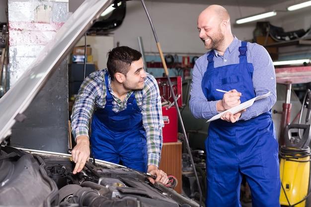 Страховой агент, измеряющий повреждение автомобиля