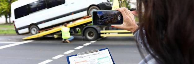 Страховой агент фиксирует аварию на своем телефоне и оценивает машину. концепция автомобильной аварии