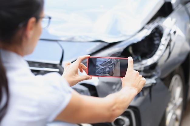 보험 대리인 여성은 교통 사고 차량 후 자동차 손상의 스마트 폰으로 사진을 찍는다