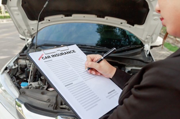 Insurance agent writing on car insurance document and examining car after accident.