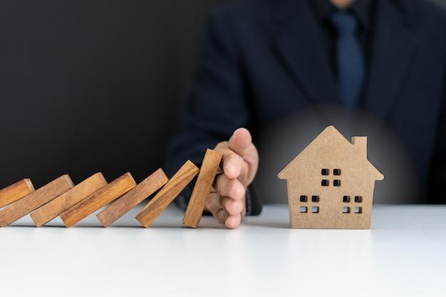 보험 대리인 또는 가족 지도자는 도미노가 집에 떨어지는 것을 방지하기 위해 손을 사용하고 있습니다. 외부 위험 방지. 주택 보험 계획