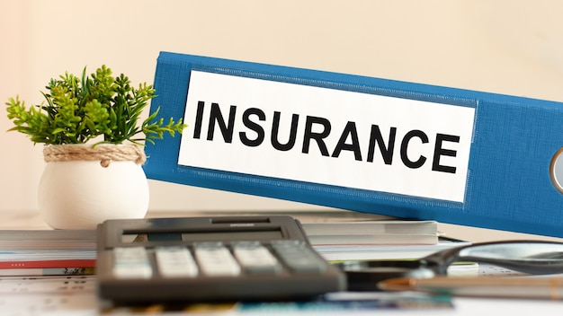 보험-계산기, 펜 및 녹색 화분 사무실에서 책상에 파란색 바인더. 비즈니스, 금융, 교육, 감사 및 세금 개념에 사용할 수 있습니다. 선택적 초점.