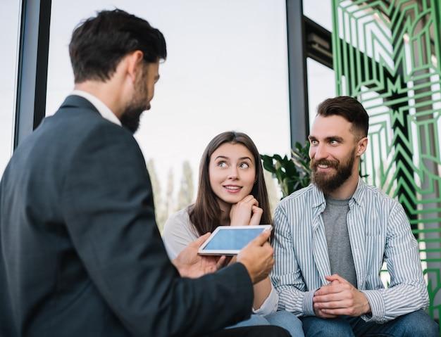 Страховой брокер советуя с молодыми парами в офисе. мужчина и женщина выбирают дом в агентстве недвижимости