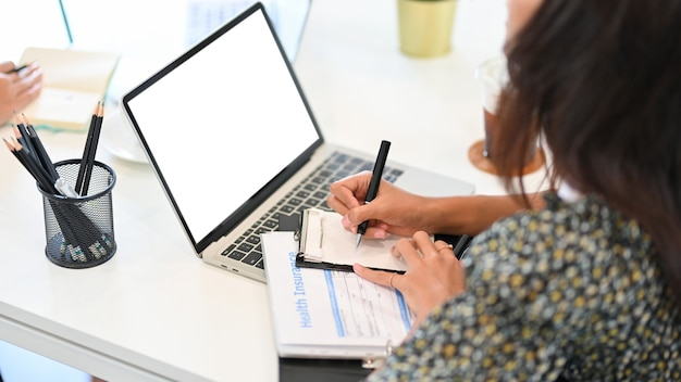 Страховой брокер делает заметки на портативном компьютере в блокнотах