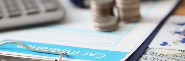 Договор страхования с монетами и игрушечной машинкой вместе с калькулятором лежат на столе