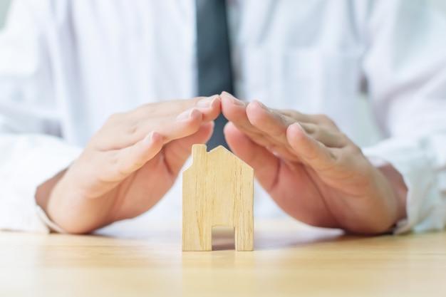 保険の家の保護の概念。男の手が木造住宅を防ぐ
