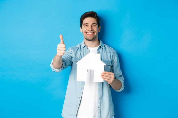 Assicurazione, mutuo e concetto immobiliare. cliente soddisfatto che mostra il modello della casa e il pollice in su, sorridendo soddisfatto, in piedi su sfondo blu.