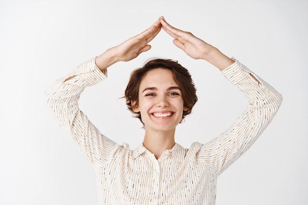 Assicurazione e concetto immobiliare. donna candida che sorride e mostra il tetto della casa con le mani sopra la testa, sembra felice, fa un gesto sul tetto, muro bianco