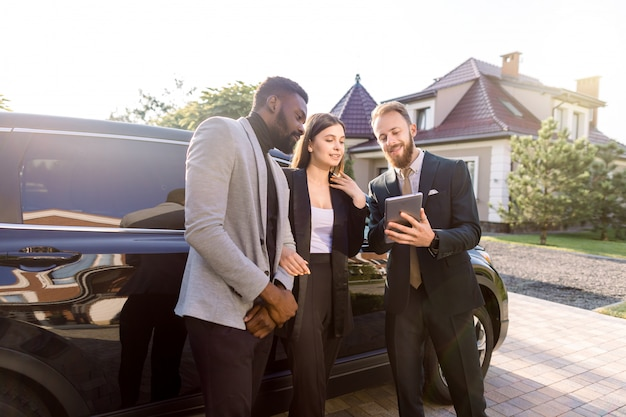 Insurance or sales agent with tablet filling contract or insurance form near black new car and talking with clients, business couple, african man and caucasian woman