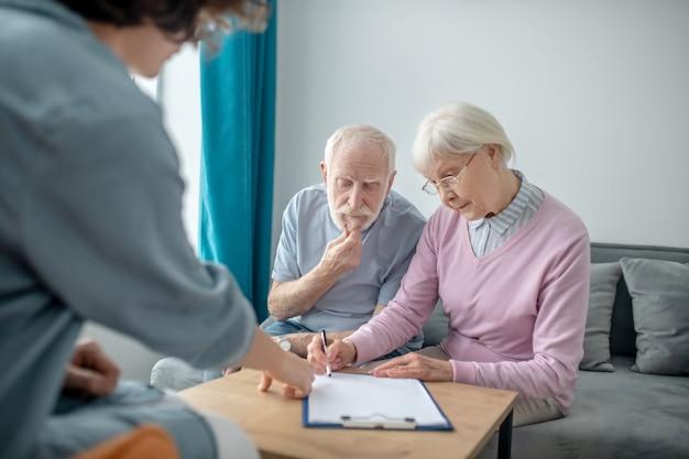 Страхование. старшая пара, назначенная на встречу с агентом медицинского страхования и подписывающая контракт