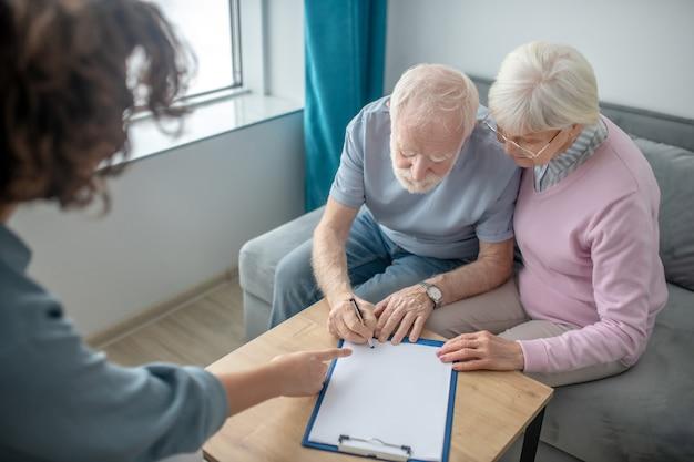 保険。健康保険代理店との約束を持ち、契約を結ぶ老夫婦