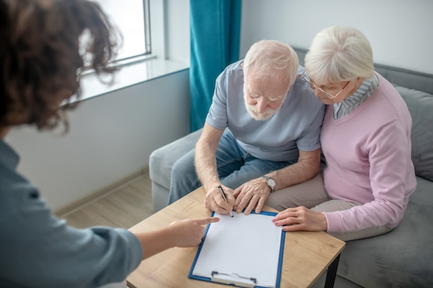Insurance. senior couple having an appointment with health insurance agent and signing the contract