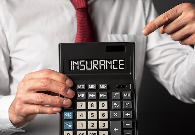 Страховой текст на калькуляторе в руках агента крупным планом