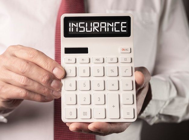 Insurance word on calculator in hands of agent in white shirt and tie