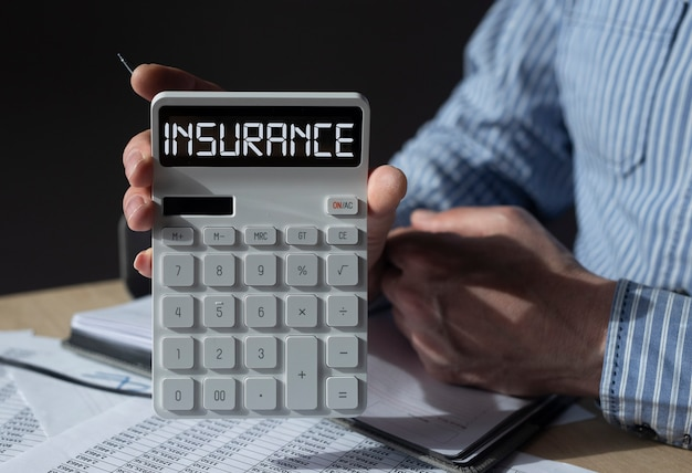 Insurance word on calculator in hands of agent