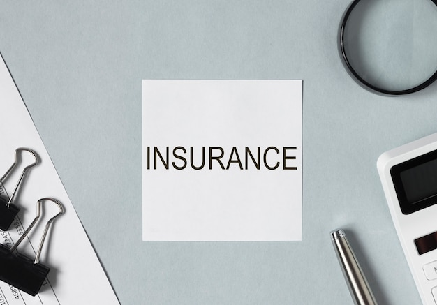 Insurance word on paper note on desk with stationery around top view