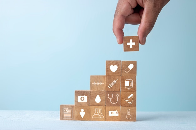 Insurance for your health and healthcare concept, businessman hand arranging wood block stacking with icon healthcare medical.
