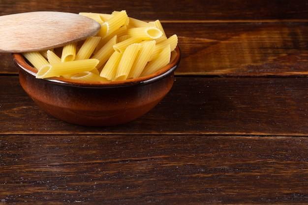 木製のテーブルの上に木のスプーンで茶色のボウルに統合ペンネ