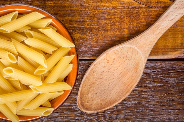 Integral penne into a brown bowl with a wooden spoon over a wooden table