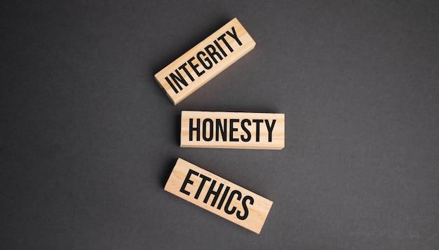 黄色の背景に木製のブロックに誠実さ、誠実さ、倫理の言葉。ビジネス倫理の概念。