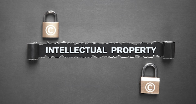 Intellectual property text on torn paper with padlocks.