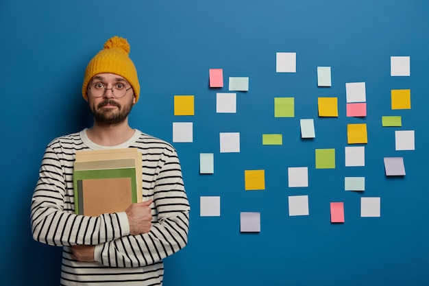 Intelligent bearded student in yellow hat, striped jumper prepares for workshop, stands with papers and notepad