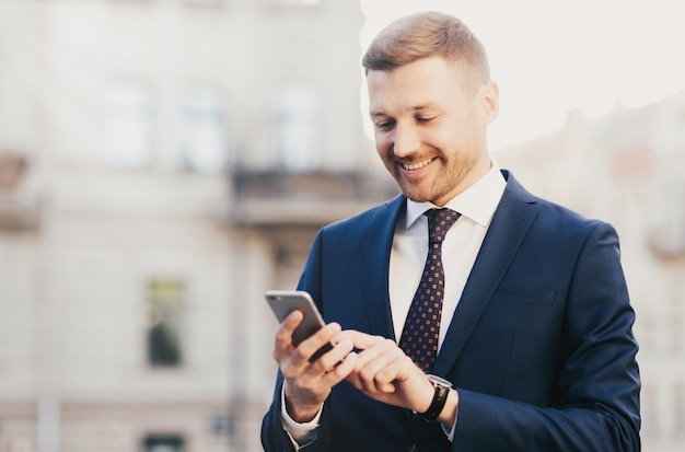 Intelligent businessman with positive expression, uses application on smart phone