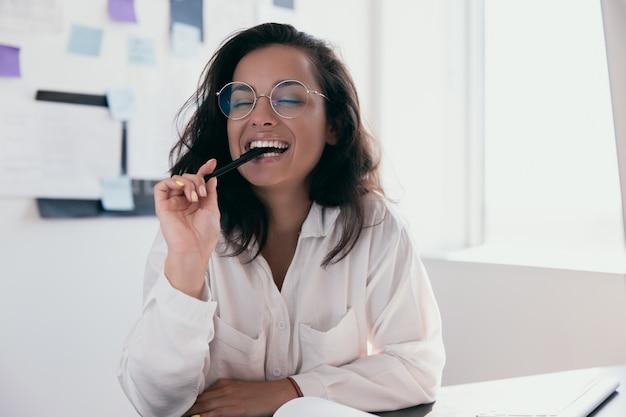知的な実業家がペンを歯で噛み、幸せそうに笑う。白いシャツと丸いメガネのオフィスまたはフリーランスの女性労働者。ポジティブシンキングパーソンコンセプト。