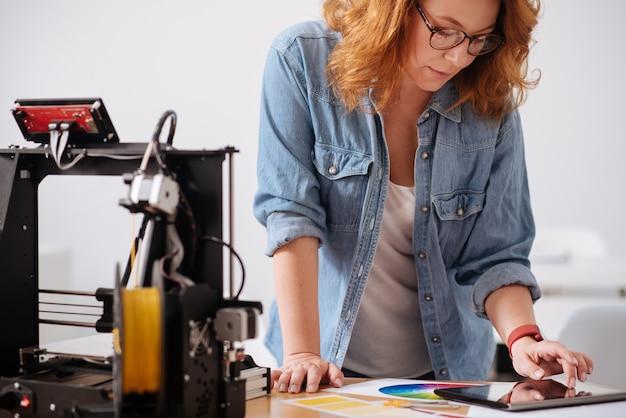 태블릿에서 작업하는 동안 테이블 근처에 서서 그것에 기대어 지능형 여성 3d 디자이너